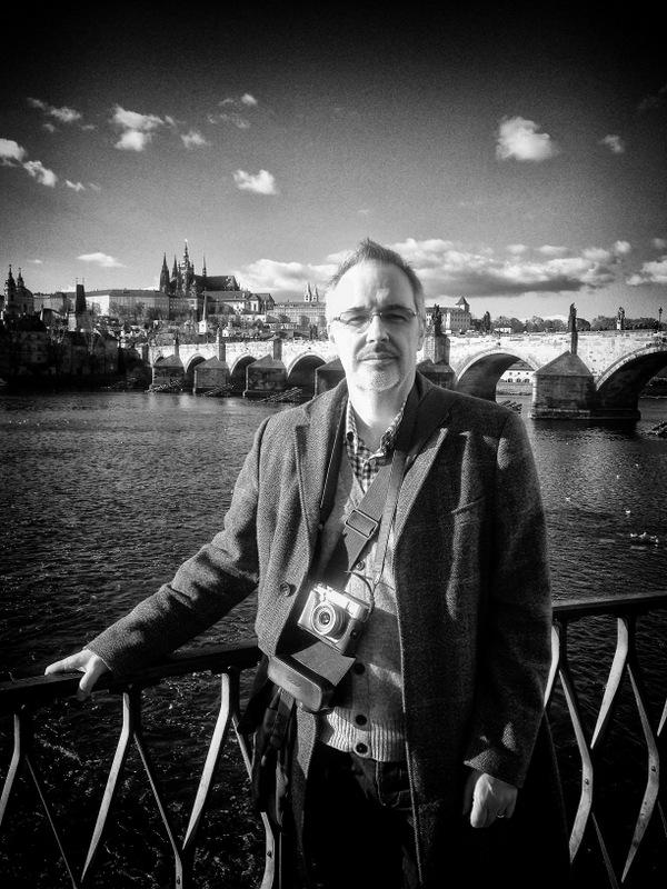 Ageing Hipster in Prague with Charles Bridge Behind